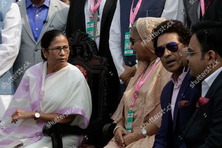 Prime Minister of Bangladesh Sheikh Hasina, center, speaks with Chief Minister of West Bengal state Mamata Banerjee, left, with former Indian cricketer Sachin Tendulkar sitting beside her prior to the start of the second test match between India and Bangladesh in Kolkata, India, . India and Bangladesh are playing their first day-night test match with a pink ball
