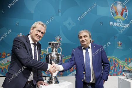 Erik Hamren (L), head coach of Iceland, shakes hands with Mihai Stoichita, Technical Director of Romania, in front of the Henri Delaunay trophy, during the drawing of the UEFA EURO 2020 Play-off matches, at the UEFA headquarters in Nyon, Switzerland, Friday, November 22, 2019.