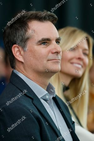 Former NASCAR champion Jeff Gordon sits next to Chandra Johnson and listens during the retirement press conference of his former teammate, NASCAR driver, Jimmie Johnson near Charlotte, N.C