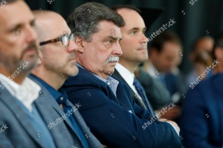 Mike Helton, vice chairman of NASCAR listens intently as Jimmie Johnson announces his retirement from racing at a press conference near Charlotte, N.C