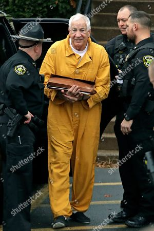 Former Penn State University assistant football coach Jerry Sandusky, center, arrives at the Centre County Courthouse, in Bellefonte, Pa., to be resentenced after an appeals court said mandatory minimum sentences had been improperly applied against him