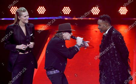 Toni Garrn, Udo Lindenberg and Billy Porter stand on stage during the International Music Award (IMA) 2019 in Berlin, Germany, 22 November 2019. The IMA recognizes the efforts of artists to share their work with a statement independently of the commercial success.