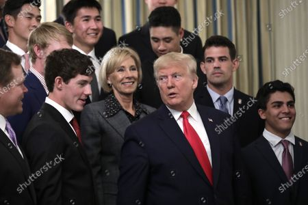 United States President Donald Trump with US Secretary of Education Betsy DeVos greets athletes from the Stanford University Men's Golf as part of NCAA Collegiate National Champions Day
