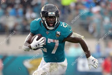 """Stock Photo of Jacksonville Jaguars running back Leonard Fournette (27) rushes for yardage against the New York Jets during the first half of an NFL football game, in Jacksonville, Fla. Fournette had a series of meetings and calls this week after carrying the ball a season-low eight times in a 20-point loss to Indianapolis. The most notable of them was chatting with 1981 Heisman Trophy winner and retired Oakland Raiders star Marcus Allen, who told the third-year pro about his experience having to play fullback and share a backfield with fellow Heisman winner Bo Jackson more than 30 years ago. """"His situation was harder than mine,"""" said Fournette, who first met Allen during a recruiting visit to USC while he was in high school"""