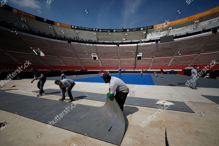 "Stock Image of Workers lay down the court surface as they transform the Plaza de Toros Mexico bullfighting ring into a tennis court, in Mexico City, . The site has already played host to motocross events, concerts, wrestling matches and boxing fights, including one with Saul ""Canelo"" Alvarez and another with Julio Cesar Chavez"