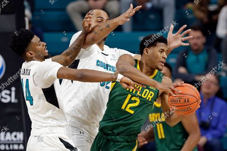 Coastal Carolina guard Malik Legania (14) and center Levi Cook (32) pressure Baylor guard Jared Butler (12) during the first half of an NCAA college basketball game at the Myrtle Beach Invitational in Conway, S.C