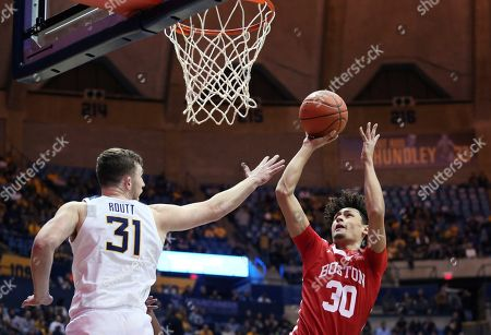 West Virginia forward Logan Routt (31) defends against Boston University guard Javante McCoy (30) during the first half of an NCAA college basketball game, in Morgantown, W.Va