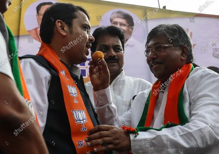 Chandrakant Patil (R), Maharashtra BJP president, gives sweets to Devendra Fadnavis (L), after he took oath as the Chief Minister of Maharashtra, at the BJP head office in Mumbai, India, 23 November 2019. Devendra Fadnavis took oath as the Chief Minister of Maharashtra along with Ajit Pawar, leader of NCP as his deputy chief minister, early morning on 23 November. The development comes after Shiv Sena, NCP and Congress make an alliance and announced that Uddhav Thackeray would be the new Chief Minister of the state and will head a government of their alliance.