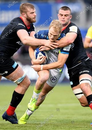 Aled Davies of Ospreys is tackled by George Kruis and Ben Earl of Saracens.