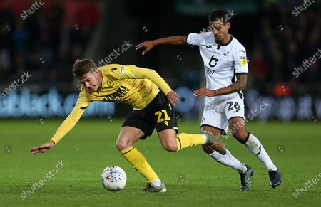Connor Mahoney of Millwall is tackled by Kyle Naughton of Swansea City.
