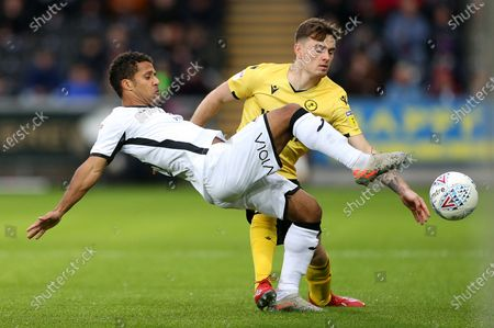 Wayne Routledge of Swansea City is tackled by Ben Thompson of Millwall.