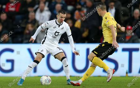 Bersant Celina of Swansea City is challenged by Shaun Williams of Millwall.