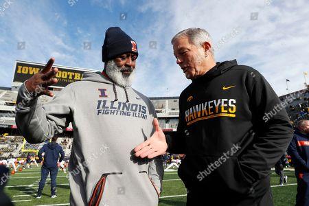 Illinois head coach Lovie Smith, left, greets Iowa head coach Kirk Ferentz before an NCAA college football game, in Iowa City, Iowa