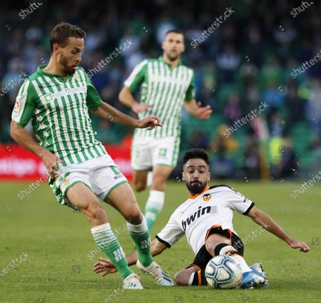 Betis' midfielder Sergio Canales (L) in action against Valencia's defender Jaume Costa (R) during the Spanish LaLiga soccer match between Real Betis and Valencia CF at Benito Villamarin stadium in Seville, Andalusia, Spain, 23 November 2019.