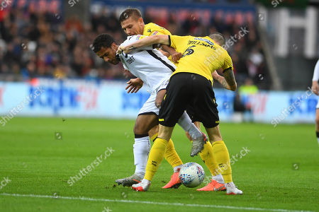 Stock Photo of Swansea player Wayne Routledge tries to get past Millwall players Shaun Williams and Shaun Hutchinson