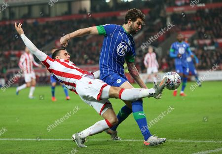Stoke City striker Lee Gregory (19) beats Wigan Athletic defender Charlie Mulgrew (16)  and crosses the ball during the EFL Sky Bet Championship match between Stoke City and Wigan Athletic at the Bet365 Stadium, Stoke-on-Trent