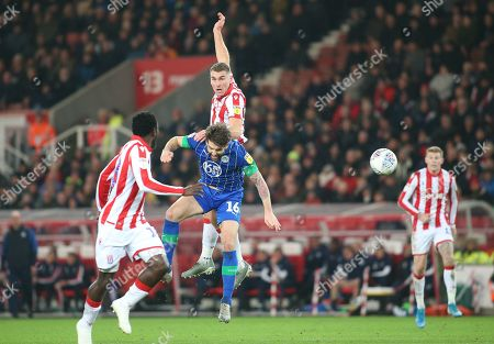 Stoke City striker Sam Vokes (9) wins a header despite being challenged by Wigan Athletic defender Charlie Mulgrew (16) during the EFL Sky Bet Championship match between Stoke City and Wigan Athletic at the Bet365 Stadium, Stoke-on-Trent