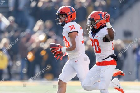 Stock Photo of Sydney Brown, Nick Walker. Illinois defensive back Sydney Brown (30) celebrates with teammate Nick Walker, right, after intercepting a pass during the first half of an NCAA college football game against Iowa, in Iowa City, Iowa