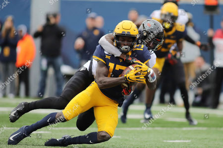 West Virginia's Sam Jones (13) is tackled at the one yard line by Oklahoma State's Braydon Johnson (8) during the first half of an NCAA college football game in Morgantown, W.Va., on
