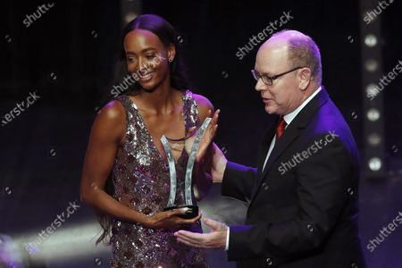 Stock Photo of World 400m hurdles champion Dalilah Muhammad (L) of USA receives the Female Athlete of the Year award from Prince Albert II of Monaco (R) during the IAAF Athletes of the Year Award Ceremony at the Grimaldi Forum in Monaco, 23 November 2019.