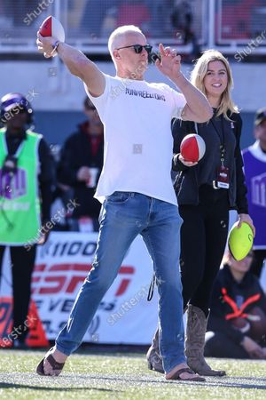 Stock Image of Kenny Mayne, an alumnus of the UNLV Rebels, throws a nerf football during a contest while attending the NCAA Football game featuring the San Jose State Spartans and the UNLV Rebels at Sam Boyd Stadium in Las Vegas, NV