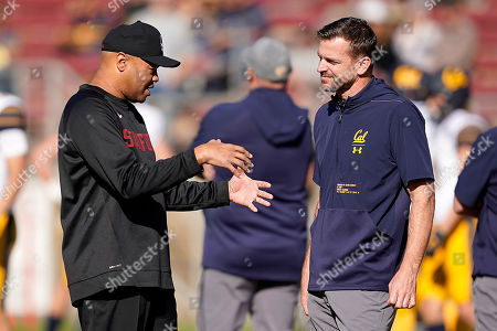 Stanford head coach David Shaw, left, talks with California head coach Justin Wilcox, right, before the first half of an NCAA game in Stanford, Calif