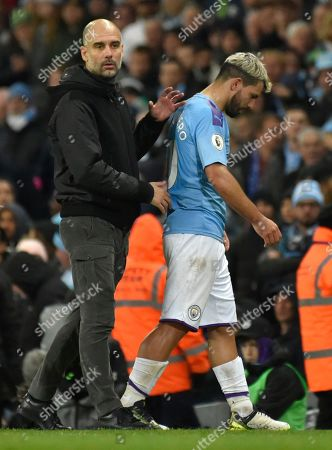Manchester City's head coach Pep Guardiola with Sergio Aguero, right, as he leaves the pitch after getting injured during the English Premier League soccer match between Manchester City and Chelsea at Etihad stadium in Manchester, England