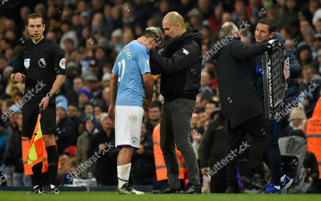 Manchester City's head coach Pep Guardiola talks with Sergio Aguero, center left, as he leaves the pitch after getting injured during the English Premier League soccer match between Manchester City and Chelsea at Etihad stadium in Manchester, England