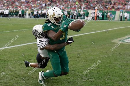 South Florida wide receiver Randall St. Felix (5) can't hang onto a pass as he is hit by Memphis defensive back T.J. Carter during the first half of an NCAA college football game, in Tampa, Fla