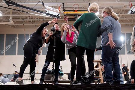 Stock Picture of Campaign staff wave their hands to get the attention of a baby as Democratic presidential candidate Sen. Elizabeth Warren, D-Mass., poses for photos in the selfie line during a campaign stop, in Manchester, N.H