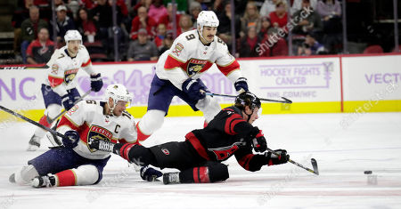 Carolina Hurricanes' Brock McGinn (23) hits the ice to play the puck against Florida Panthers' Aleksander Barkov (16), of Finland, and Brian Boyle (9) during the second period of an NHL hockey game in Raleigh, N.C