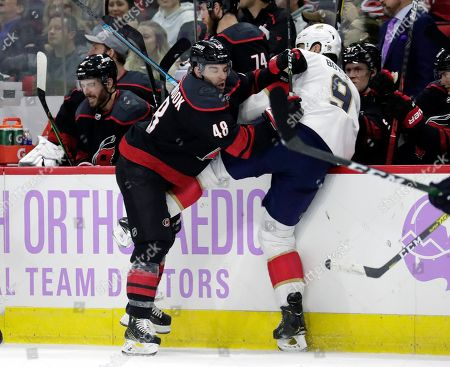 Carolina Hurricanes' Jordan Martinook (48) checks Florida Panthers' Brian Boyle (9) into the boards during the second period of an NHL hockey game in Raleigh, N.C