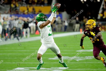 Oregon wide receiver Johnny Johnson III (3) pulls in a catch next to Arizona State's Chase Lucas during the first half of an NCAA college football game, in Tempe, Ariz