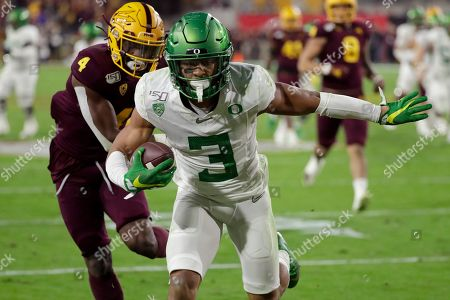 Oregon wide receiver Johnny Johnson III (3) scores a touchdown as Arizona State defensive back Evan Fields (4) defends during the second half of an NCAA college football game, in Tempe, Ariz. Arizona State won 31-28