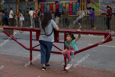 Stock Photo of A woman watches voters line up to go into a polling station as a child rests on a barrier in Tseung Kwan O district, Hong Kong, . Long lines snaked around plazas and extended for blocks as citizens of the semi-autonomous Chinese territory turned out in droves Sunday for an election seen as a test of public support for anti-government protests that have persisted for more than five months