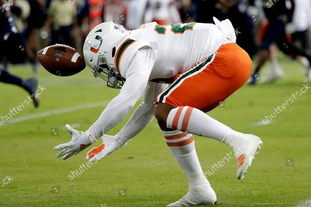 Miami running back Cam'Ron Harris cannot hold onto the football during the first half of an NCAA college football game against Miami, in Miami