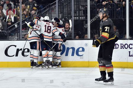 Edmonton Oilers defenseman Oscar Klefbom (77), left wing James Neal (18) and center Gaetan Haas (91) celebrate after Connor McDavid, obscured, scored against the Vegas Golden Knights during the third period of an NHL hockey game, in Las Vegas