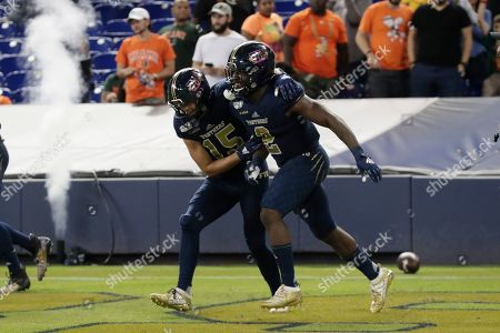 FIU running back Anthony Jones (2) celebrates with wide receiver Austin Maloney (15) after scoring a touchdown during the second half of an NCAA college football game against Miami, in Miami. FIU won 30-24