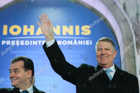 Romanian President Klaus Iohannis, right, waves next to Romanian prime minister Ludovic Orban, after exit polls were published, in Bucharest, Romania, . An exit poll by the IRES independent think tank showed Iohannis getting 66.5 % of the votes, with 33.5% for Social Democratic Party leader Viorica Dancila, a former prime minister