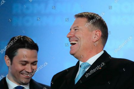 Romanian President Klaus Iohannis, laughs after exit polls were published, in Bucharest, Romania, . An exit poll by the IRES independent think tank predicts Iohannis getting 66.5 % of the votes, with 33.5% for Social Democratic Party leader Viorica Dancila, a former prime minister