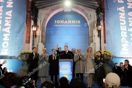 Romanian President Klaus Iohannis waves after exit polls were published, in Bucharest, Romania, . An exit poll by the IRES independent think tank predicts Iohannis getting 66.5 % of the votes, with 33.5% for Social Democratic Party leader Viorica Dancila, a former prime minister