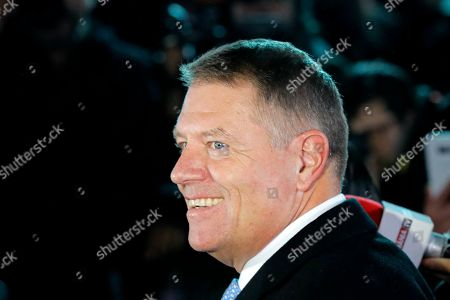 Romanian President Klaus Iohannis smiles exit polls were published, in Bucharest, Romania, . An exit poll by the IRES independent think tank showed Iohannis getting 66.5 % of the votes, with 33.5% for Social Democratic Party leader Viorica Dancila, a former prime minister