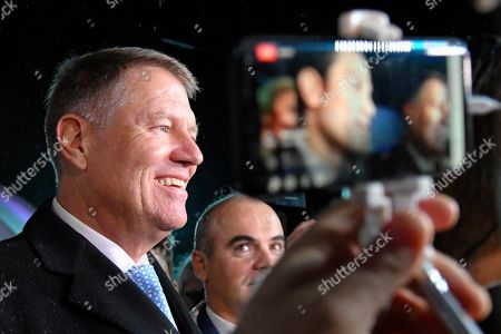 Romanian President Klaus Iohannis is surrounded by media after exit polls were published, in Bucharest, Romania, . An exit poll by the IRES independent think tank showed Iohannis getting 66.5 % of the votes, with 33.5% for Social Democratic Party leader Viorica Dancila, a former prime minister