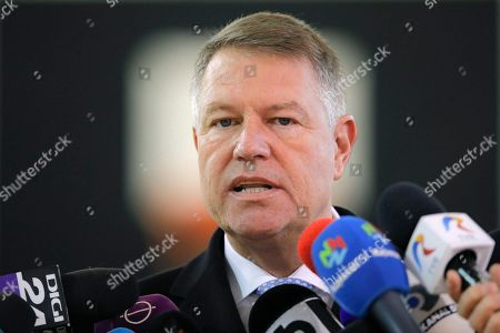 Romanian President Klaus Iohannis speaks to the media after casting his vote in Bucharest, Romania, . Romanians are voting in a presidential runoff election in which incumbent Klaus Iohannis is vying for a second term, facing Social Democratic Party leader Viorica Dancila, a former prime minister, in Sunday's vote