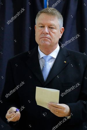 Romanian President Klaus Iohannis exits a voting cabin in Bucharest, Romania, . Romanians are voting in a presidential runoff election in which incumbent Klaus Iohannis is vying for a second term, facing Social Democratic Party leader Viorica Dancila, a former prime minister, in Sunday's vote
