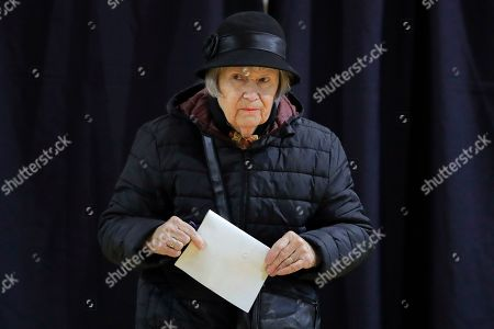 A woman exits a voting cabin in Bucharest, Romania, . Romanians are voting in a presidential runoff election in which incumbent Klaus Iohannis is vying for a second term, facing Social Democratic Party leader Viorica Dancila, a former prime minister, in Sunday's vote