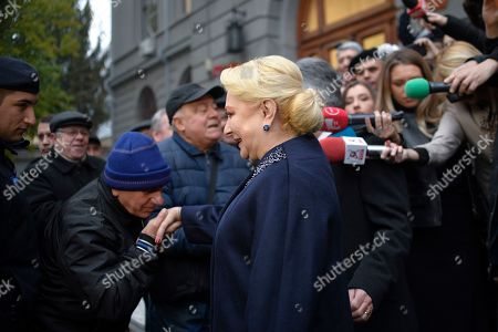 Former Prime Minister and presidential candidate for the Social Democratic party Viorica Dancila is greeted by supporters outside a voting station in Bucharest, Romania, . Romanians are voting in a presidential runoff election in which incumbent Klaus Iohannis is vying for a second term