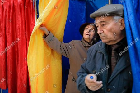 People exit voting cabins with curtains in the colors of the country's national flag in Bucharest, Romania, . Romanians are voting in a presidential runoff election in which incumbent Klaus Iohannis is vying for a second term, facing Social Democratic Party leader Viorica Dancila, a former prime minister, in Sunday's vote