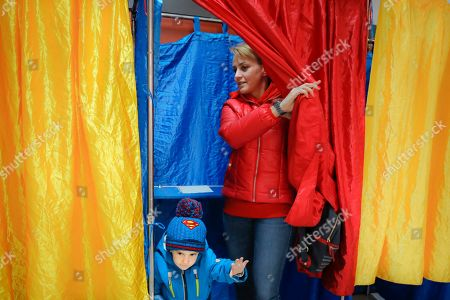 A woman and child exit a voting cabin with curtains in the colors of the country's national flag in Bucharest, Romania, . Romanians are voting in a presidential runoff election in which incumbent Klaus Iohannis is vying for a second term, facing Social Democratic Party leader Viorica Dancila, a former prime minister, in Sunday's vote