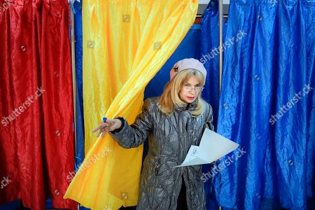 A woman exits a voting cabin with curtains in the colors of the country's national flag in Bucharest, Romania, . Romanians are voting in a presidential runoff election in which incumbent Klaus Iohannis is vying for a second term, facing Social Democratic Party leader Viorica Dancila, a former prime minister, in Sunday's vote